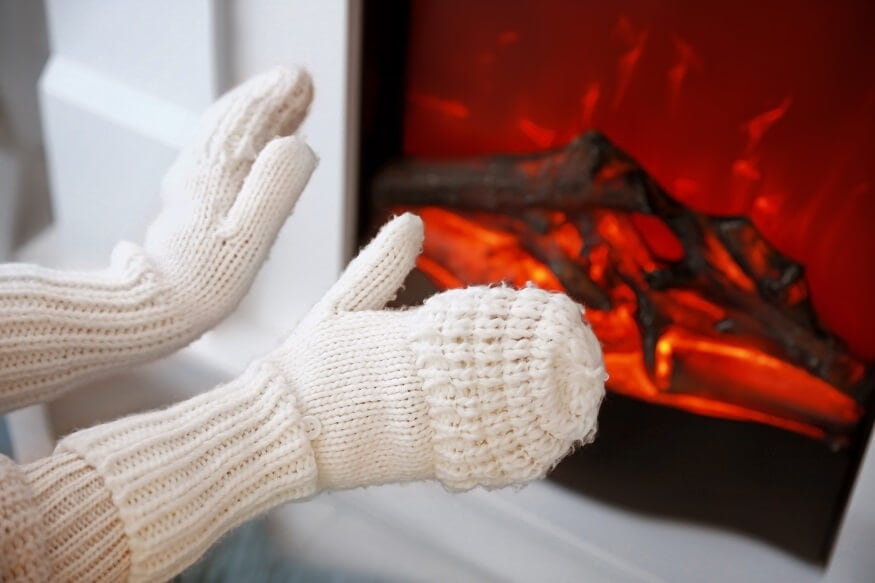 woman's hands warming up next to an electric fireplace