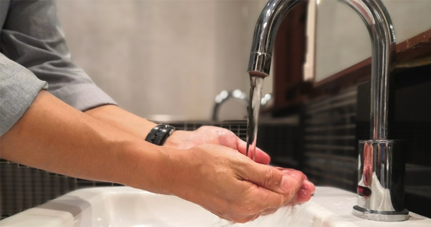 man washing hands using a touchless kitchen faucet
