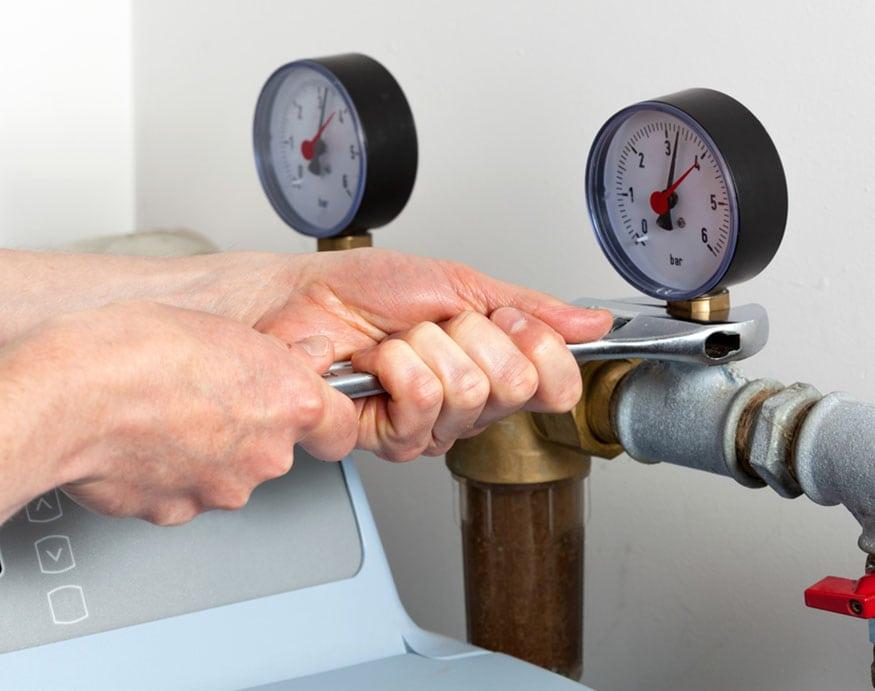 plumber adjusting the pressure gauge