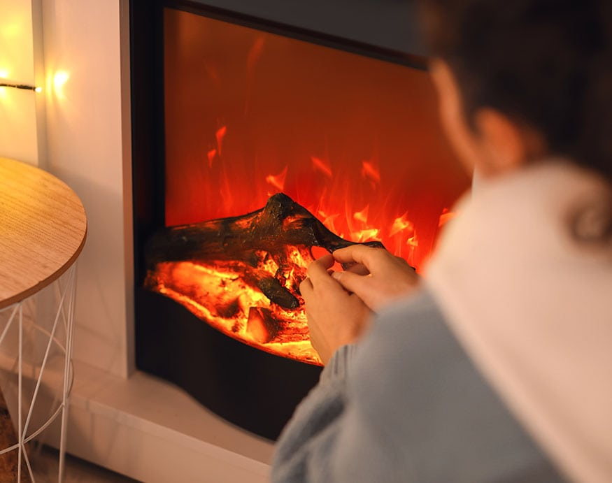 woman sitting next to an electric fireplace