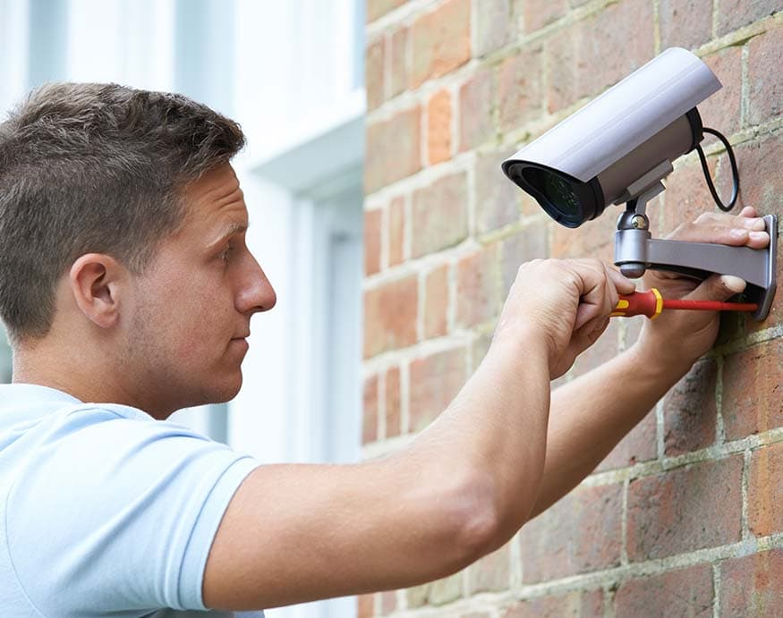 A person installing a security camera