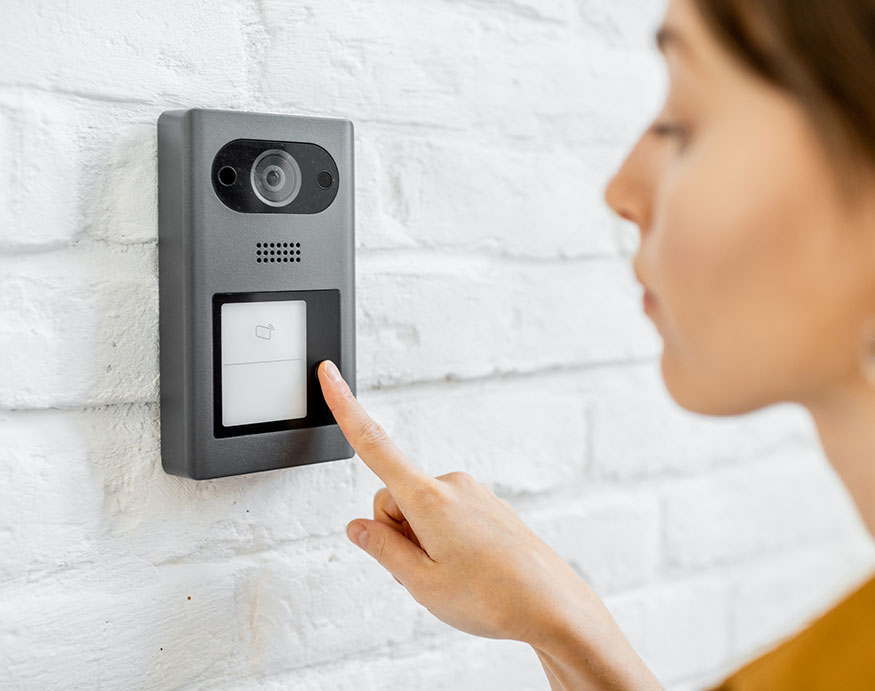 Woman pressing the button of a video doorbell camera