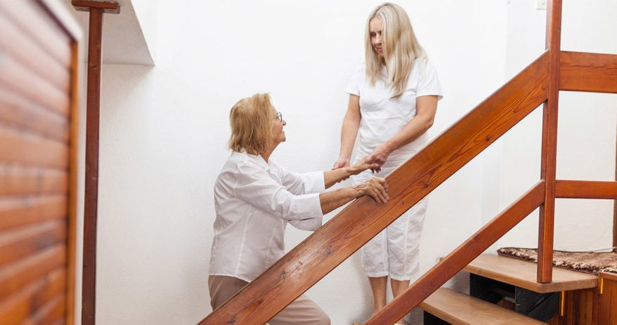woman helping elderly person up the stairs